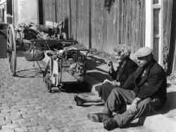 [Un couple assis sur le trottoir, deux carrioles à leur côté]