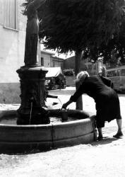 [Une vieille dame remplit un petit arrosoir à la fontaine d'un village]