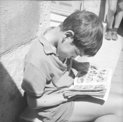 [Un enfant lit une bande dessinée]