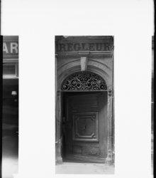 [20, rue Palais-Grillet : portail avec imposte à volutes et porte à compartiments]