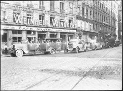 [Cars Berliet devant le restaurant Bellecour, à l'extrémité sud de la rue de l'Hôtel-de-Ville et à proximité de la place Bellecour]