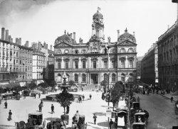 [Place des Terreaux et hôtel de ville de Lyon : fiacres et passants autour de la fontaine centrale]