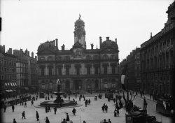 [Place des Terreaux et hôtel de ville de Lyon : fiacres, tramways à cheval et passants autour de la fontaine centrale]