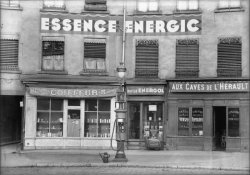 """[Devantures de magasins : coiffeur, station service et café """"Aux caves de l'Hérault""""]"""