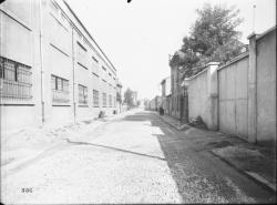 [Rue de Villeurbanne, bordée d'un bâtiment industriel et de maisons]