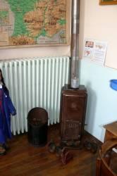 Le poêle à charbon devant lequel sèchent les sabots et les galoches