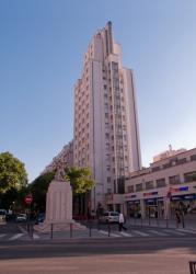 """La statue """"Le Répit"""" sur le carrefour avenue Henri-Barbusse - cours Emile-Zola et une des tours des Gratte-Ciel"""