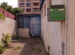 Terrain en friche avec un appentis en tôle ondulée sur la rue Léon-Chomel