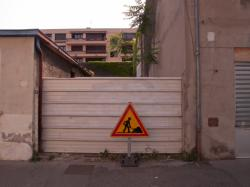 Un immeuble voué à la démolition et un terrain condamné par une tôle ondulée rue Léon-Chomel