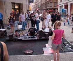 Un peintre de rue entouré par la foule rue de la République
