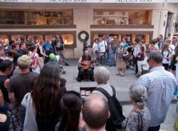 Un musicien jouant du luth et chantant entouré par la foule rue de la République