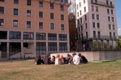 Groupe de personnes assises sur la pelouse place Louis-Pradel