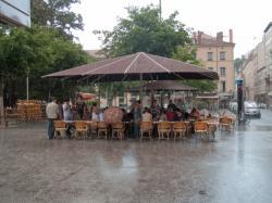 Personnes sous un abri à la terrasse d'un café place Carnot pendant un orage