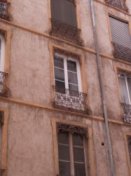Fenêtres avec balcon, jalousie et lambrequin à la lyonnaise sur un immeuble rue Sébastien-Gryphe