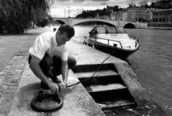 Sur le bas-port un homme accroche l'amarre de son bateau-taxi.