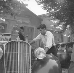 [Négociation : Un client regarde attentivement le moteur de la voiture]