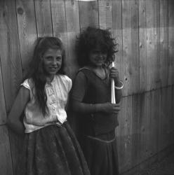 [Deux jeunes filles tsiganes adossées à un mur sourient]