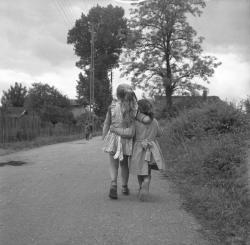 [Deux petites filles, de dos, bras dessus, bras dessous, marchent sur un chemin de campagne]