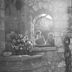[Deux filles posent dans l'encadrement d'une fenêtre]