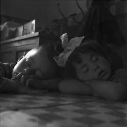 [Un garçon et une fille endormis côte à côte sur une table]