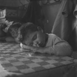 [Un petit garçon dort sur la table un doigt dans le nez]