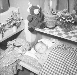 [Un enfant endormi, un ours et une poupée à proximité]