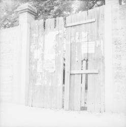 [Porte d'entrée en bois abîmée avec affiche et croix]