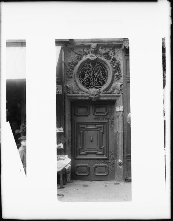 [28, rue Confort : porte d'allée à compartiments surmontée d'un imposte à oculus sculpté]