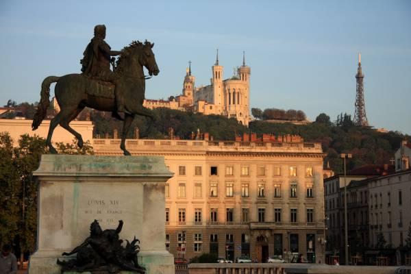 Place Bellecour. Statue de Louis XIV. Vue de Fourvière et de la Tour métallique en arrière plan.