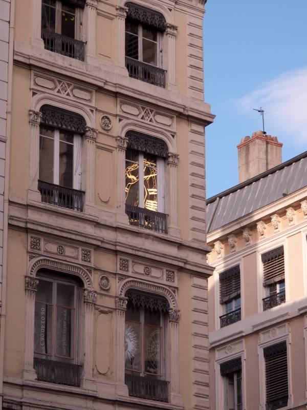 Immeuble place Saint-Nizier avec reflet de l'horloge de l'église sur les vitres.