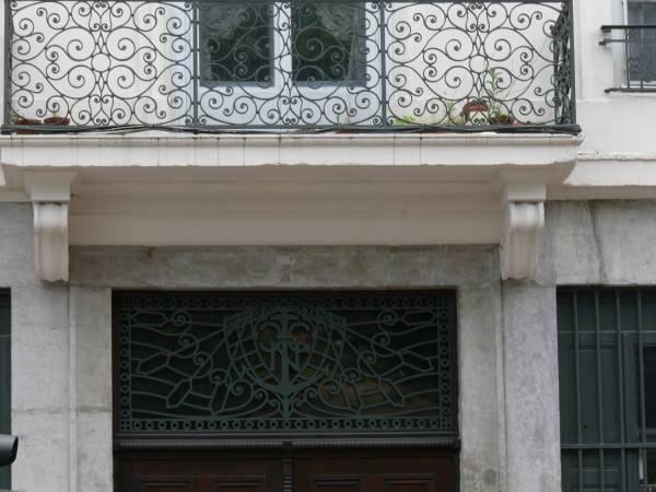 Entrée d'immeuble : imposte et balustrade en fer forgé
