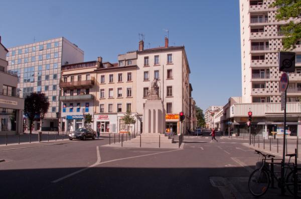 """La statue """"Le Répit"""" sur le carrefour avenue Henri-Barbusse - cours Emile-Zola, au fond la rue Léon-Chomel"""