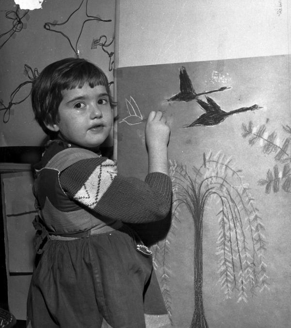 [Une petite fille dessine un dernier oiseau sur sa toile]
