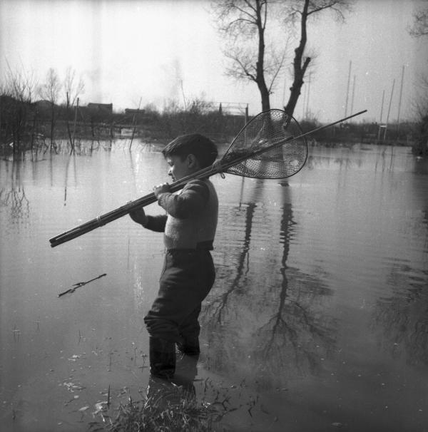 [Un garçon en bottes dans la rivière porte sur l'épaule des cannes à pêche]