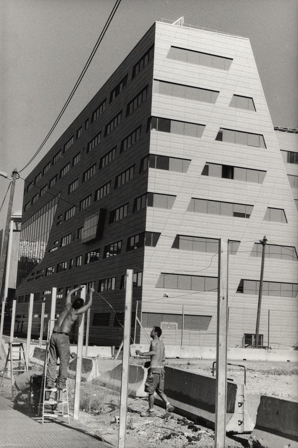 Nouvel hôtel de la région Rhône-Alpes: ouvriers installant une clôture autour de l'ancien marché-gare
